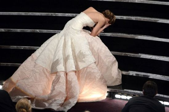 Best Actress winner Jennifer Lawrence trips up the stairs as she accepts her Oscar.(photo credit: Kevin Winter/Getty Images North America)