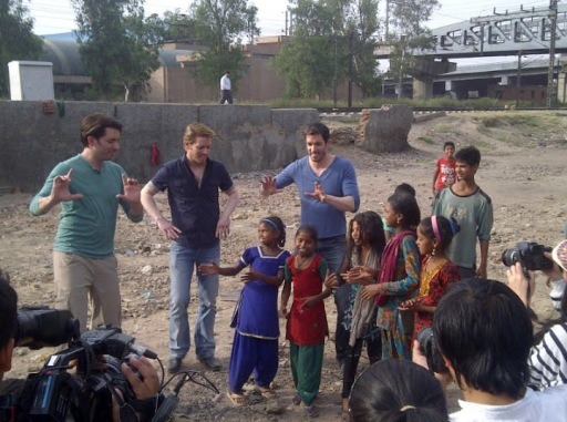 Scott brothers Jonathan, JD and Drew in New Delhi at World Vision education project being taught a cultural dance by local children. Image Credit: World Vision/Scott Brothers Entertainment